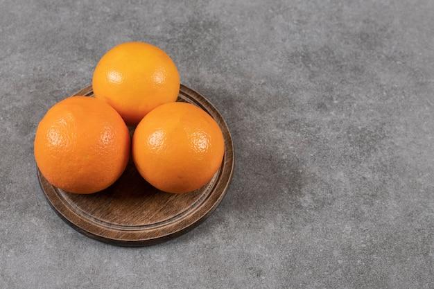 Feche foto de laranjas maduras na placa de madeira mesa cinza.