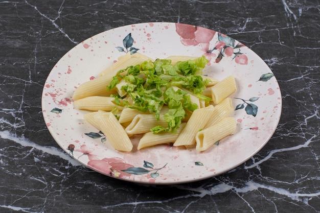 Feche foto de macarrão penne fresco com verduras.