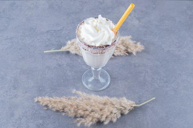 Feche foto de milk-shake cremoso em fundo cinza.
