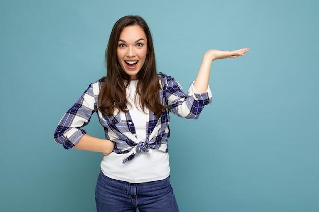 Feche foto de positiva feliz incrível fofa encantadora jovem segurando a mão e mostrando