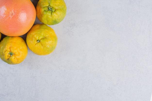 Feche fotos de tangerinas (laranjas, clementinas, frutas cítricas) sobre um fundo cinza.