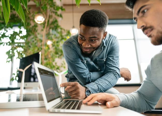 Feche homens olhando para um laptop