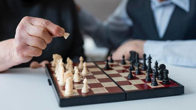 Feche idosos jogando xadrez
