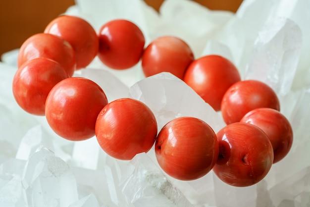 Feche lindas contas redondas de coral vermelhas preciosas sobre fundo de quartzo