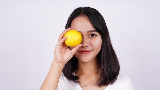 Feche lindas mulheres asiáticas com um limão isolado na superfície branca