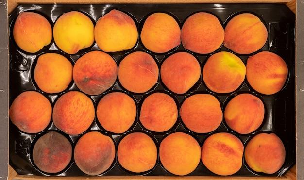 Feche lindos pêssegos crus frescos em uma caixa de madeira