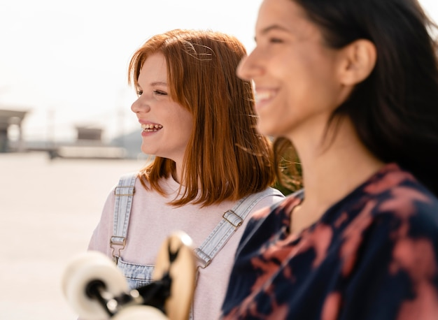 Feche mulheres sorridentes com longboard