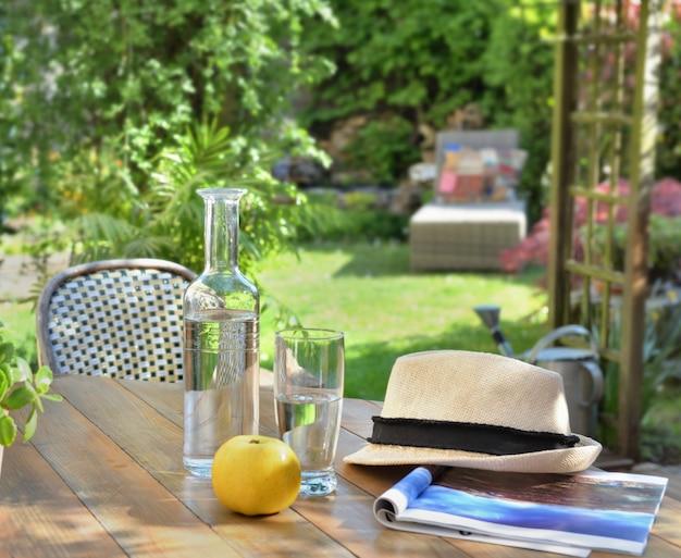 Feche na bebida e maçã em uma mesa de madeira no fundo do jardim no verão