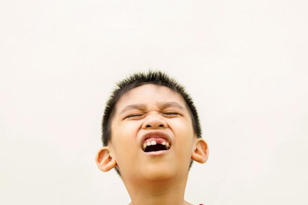 Feche na frente de um menino cantando de dor por causa da dor de dente.