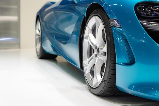 Feche na frente do carro azul novo com estacionamento de roda de liga de magnésio na sala de exposições do carro.