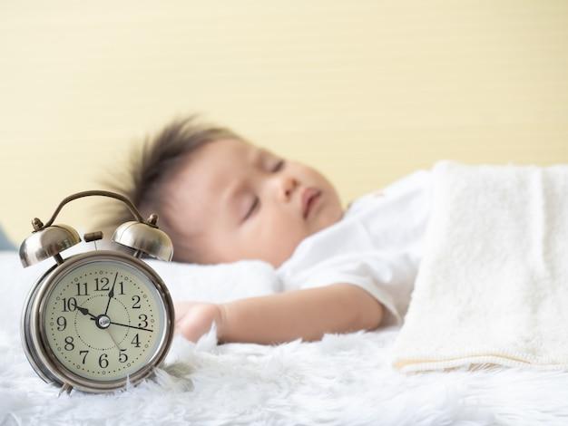 Feche no despertador e turva de menino enquanto dorme na cama.