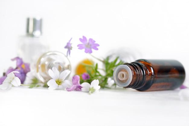 Feche no frasco derramado de óleo essencial na mesa branca e pétalas de flores