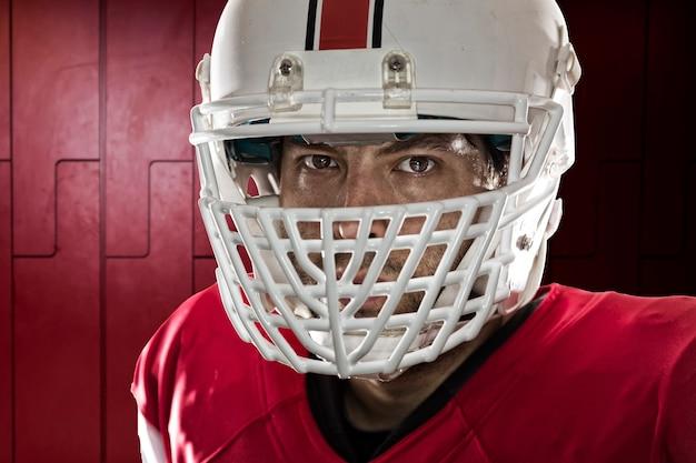 Feche nos olhos de um jogador de futebol com um uniforme vermelho em um armário.