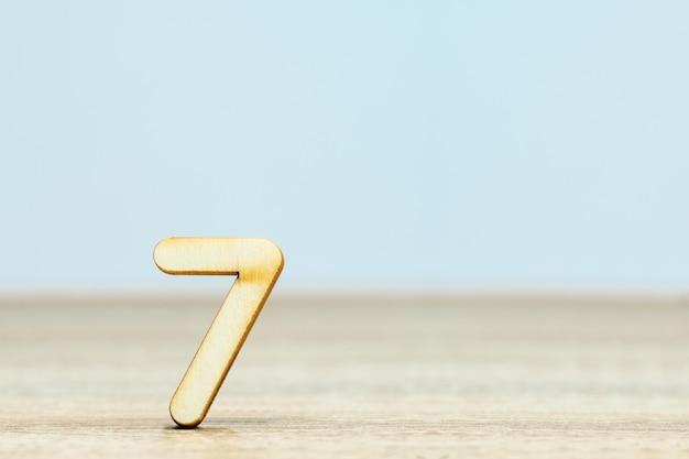 Feche numérico de madeira na mesa com espaço de cópia, número sete