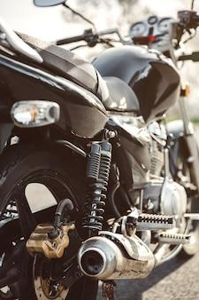 Feche o amortecedor, o tubo de escape e o freio a disco da motocicleta preta brilhante