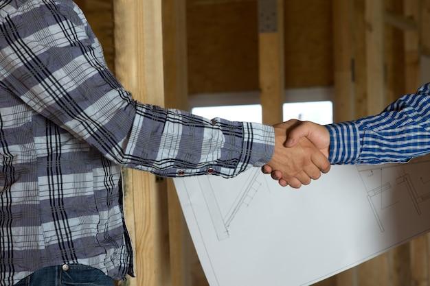 Feche o arquiteto e o cliente em ambas as camisas de manga comprida, mostrando o aperto de mão com a planta no fundo. enfatizando o projeto aprovado.