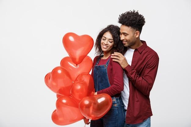 Feche o atraente casal afro-americano, abraçando e segurando um balão de coração vermelho.