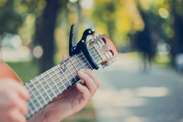 Feche o braço da guitarra com o capo no parque homem sentado no banco do parque tocando violão
