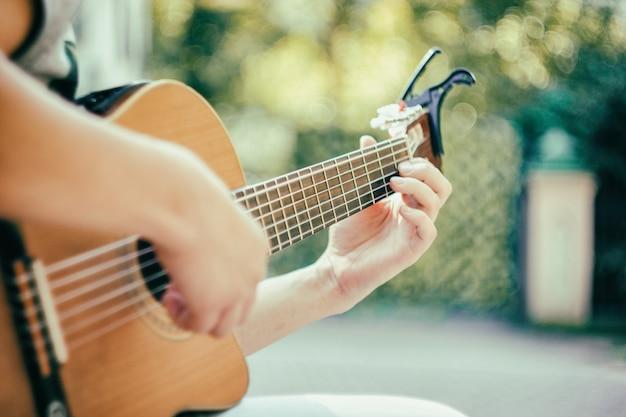 Feche o braço da guitarra com o capo no parque jovem sentado no banco tocando violão