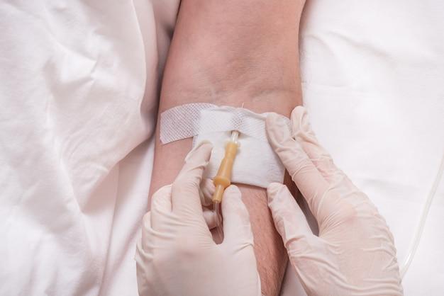 Feche o braço do homem com terapia intravenosa