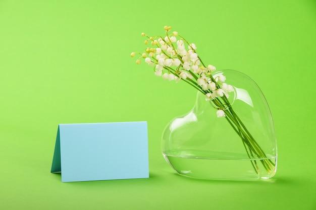Feche o buquê de lírio do vale em um vaso de vidro transparente em forma de coração e uma mensagem de cartão sobre a parede verde