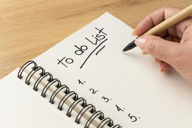 Feche o caderno com a lista de tarefas na mesa