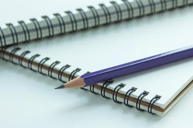 Feche o caderno espiral e lápis, ponto de foco seletivo