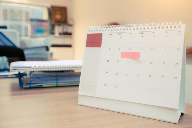 Feche o calendário de mesa com nota de papel no escritório para eventos.