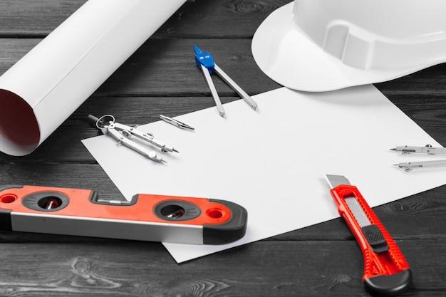 Feche o capacete de segurança branco e a variedade de ferramentas de reparo com espaço de cópia no meio sobre madeira
