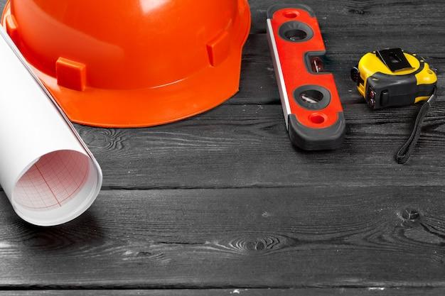 Feche o capacete de segurança laranja e a variedade de ferramentas de reparo com espaço de cópia no meio sobre madeira