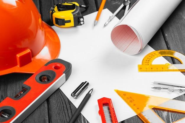 Feche o capacete de segurança laranja e variedade de ferramentas de reparo