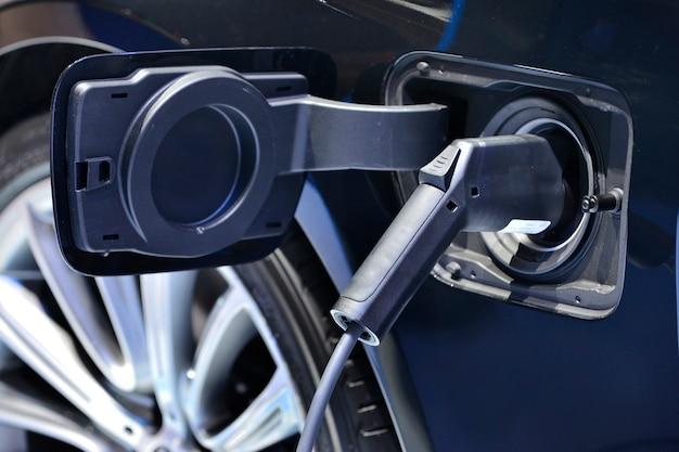 Feche o carregamento do veículo elétrico na estação com a fonte de alimentação conectada a um carro elétrico sendo carregado.