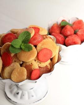 Feche o carrinho do bolo com minúsculos cereais panqueca com morangos, limão e folhas de hortelã em um fundo branco. comida da moda. mini panquecas de cereais. orientação retrato