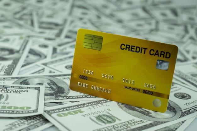 Feche o cartão de crédito isolado na pilha de notas de 100 dólares fundo