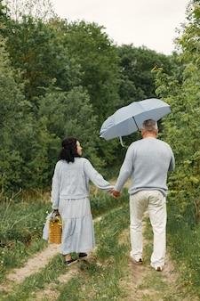 Feche o casal romântico caminhando em um parque de outono. homem e mulher vestindo blusas azuis. homem segurando um guarda-chuva.
