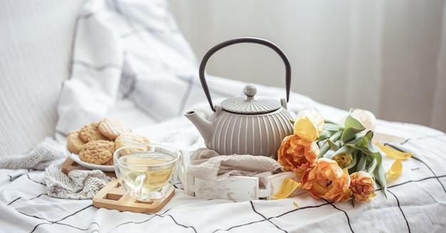 Feche o chá, biscoitos e um buquê de tulipas frescas na cama