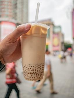 Feche o chá da bolha na mão de um turista caminhando pela rua na china