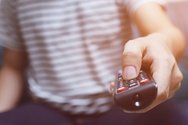 Feche o controle remoto da televisão nas mãos de um homem casual, apontando para o aparelho de tv e ligando ou desligando-o. selecione o canal assistindo tv em seu sofá em casa na sala relaxar.