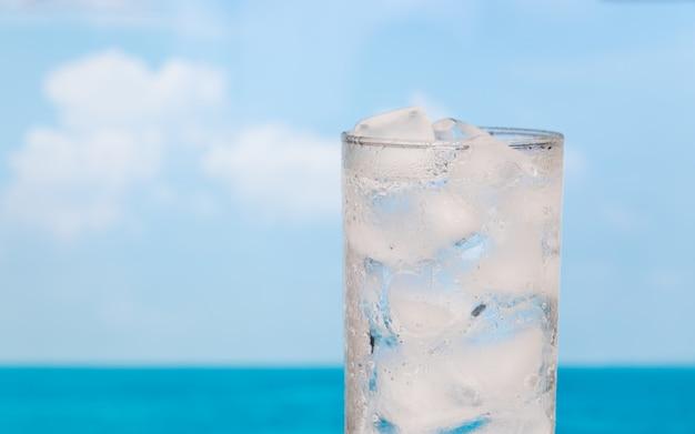 Feche o copo de refresco de beber água com gelo sobre o céu do mar de verão