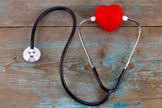 Feche o coração vermelho e estetoscópio na mesa de madeira
