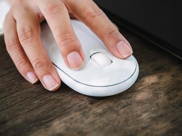 Feche o dedo usando um mouse sem fio branco moderno enquanto trabalha no laptop preto na mesa de madeira