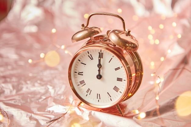 Feche o despertador pintado de dourado com tempo de natal é meia-noite em um fundo abstrato brilhante de cobre com festão, copie o espaço. cartão de felicitações.