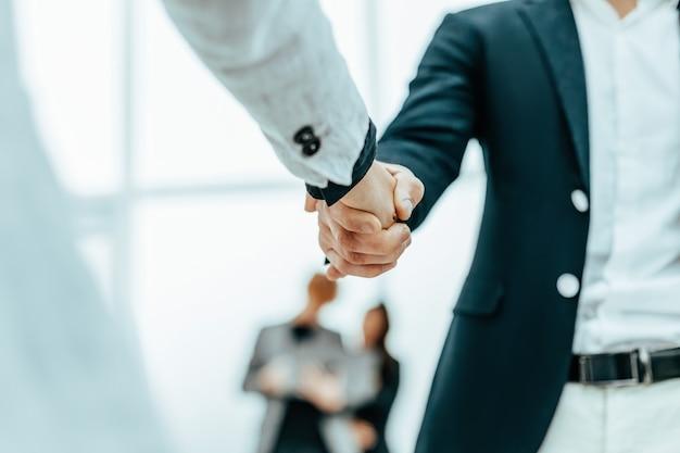 Feche o empresário e a empresária apertando as mãos um do outro