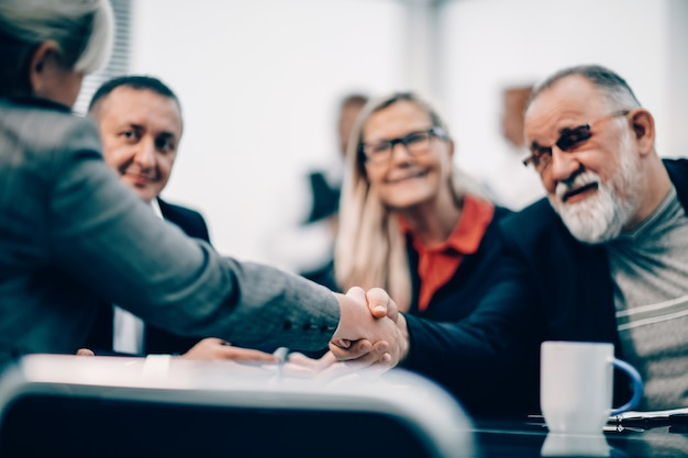 Feche o empresário e a empresária apertando as mãos