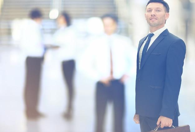 Feche o empresário em um terno preto com uma pasta no escritório borrado.