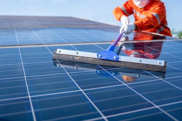 Feche o esfregão da equipe de operação use um esfregão trabalhando na limpeza da planta solar para um bom desempenho no serviço do plano de operação, conceito de limpeza de painéis solares