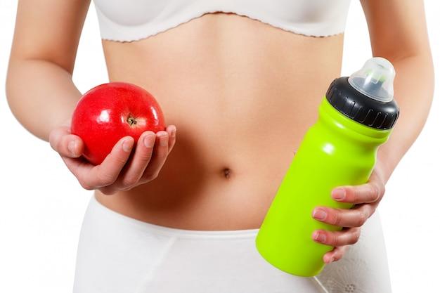 Feche o estômago da mulher com as mãos segurando a água e reg apple isolado no branco