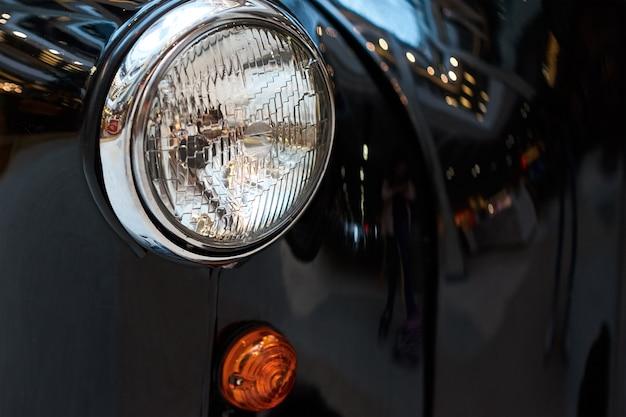Feche o farol de um carro antigo preto