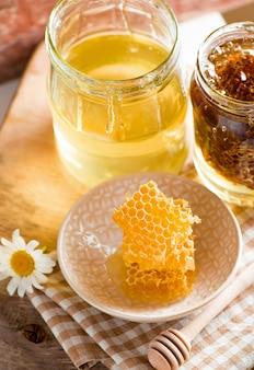 Feche o favo de mel com mel em frasco de vidro na placa de madeira, vista superior