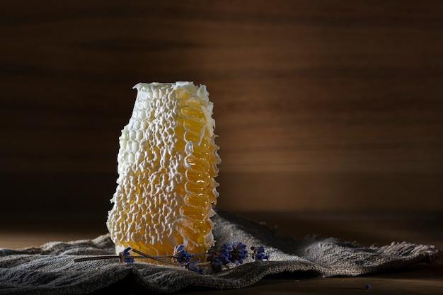 Feche o favo de mel. flores de favo de mel e lavanda em uma velha mesa de madeira. fundo escuro.